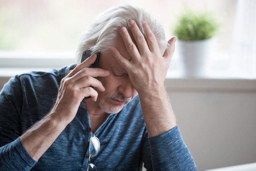 man on phone experiencing anguish